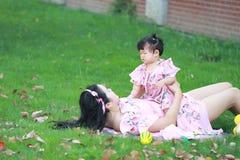 Moderleklekar med hennes litet behandla som ett barn flickan på gräsmattan Royaltyfri Foto