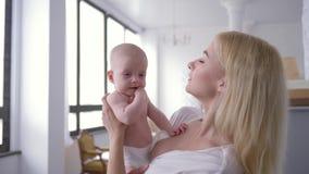 Moderlig mjukhet som älskar den nyfödda moderkeln, behandla som ett barn flickan på händer och försiktigt att kyssa henne hemma stock video