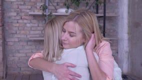 Moderlig omsorg, den älskvärda vuxna flickadottern talar med förälskelsemamma och att krama, medan koppla av hemma i säng stock video