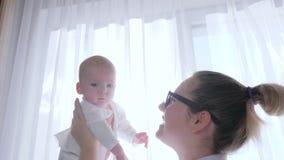 Moderlig omsorg, kvinnlig spelas med nyfött i armar i solljus inomhus nära fönster stock video