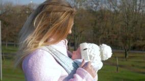 Moderlig omsorg, sjungande sång för lycklig mum för spädbarn i rem på naturen i varmt väder arkivfilmer
