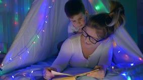 Moderlig omsorg, ung mamma och sonläsebok som inomhus ligger i tält med den ljusa festoonen stock video