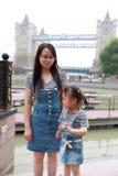 Modermammahållen hennes dotterleendeskratt har gyckel att tycka om fri tid i sommar parkerar lycklig barnbarndomlek arkivbild
