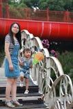 Modermammahållen hennes dotterleendeskratt har gyckel att tycka om fri tid i sommar parkerar lycklig barnbarndomlek arkivfoton