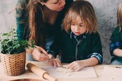 Modermatlagning med ungar i kök Litet barnsyskon som tillsammans bakar och spelar med hemmastadd bakelse Royaltyfri Bild