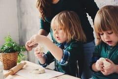 Modermatlagning med ungar i kök Litet barnsyskon som tillsammans bakar och spelar med hemmastadd bakelse royaltyfria bilder