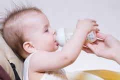 Modermatningar behandla som ett barn från en flaska av mjölkar Arkivbilder