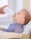 Modermatningar behandla som ett barn från en flaska av mjölkar Fotografering för Bildbyråer