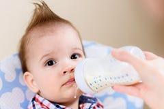 Modermatningar behandla som ett barn från en flaska av mjölkar Royaltyfria Foton