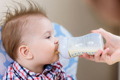 Modermatningar behandla som ett barn från en flaska av mjölkar Royaltyfri Foto