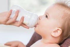 Modermatningar behandla som ett barn från en flaska av mjölkar Royaltyfri Bild