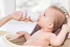 Modermatningar behandla som ett barn från en flaska av mjölkar Royaltyfria Bilder