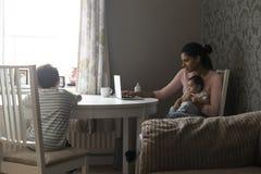 Modermång--tasking arbete och barn Fotografering för Bildbyråer