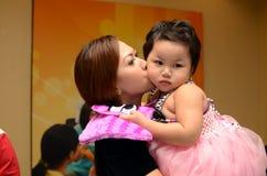 Modern är kyssande hennes förtjusande behandla som ett barn flickan Minnesvärda bilder royaltyfria foton