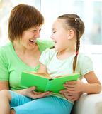 Modern är läseboken med hennes dotter royaltyfri foto