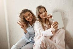 Modern är min bästa vänför evigt Charmig caucasian dotter i pyjamas som tar selfie med mamman som använder den digitala minnestav royaltyfria foton