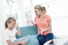 Modern är passionerad om att arbeta på en bärbar dator Döttrar har inte nog uppmärksamhet från moder arkivbild