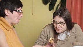 Modern äter kakan och hennes dotter som dricker kaffe Kök skratt, konversation Kvinnor med exponeringsglas stock video