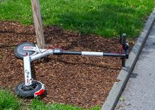 Modern сity transport - electric scooters is lying on the lawn. Modern city transport - electric scooters is lying on the lawn royalty free stock photography