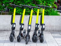Modern city transport - Five electric scooters are parked on the street of the city. Modern transport - Five electric scooters are parked on the street of the stock image