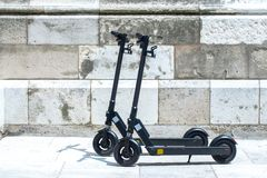 Modern сity transport - Two electric scooters is parked on the street of the city stock photography