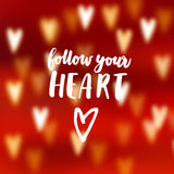 Modern abstract blurred red background with bokeh effect hearts. Follow your heart hand lettered text. Love concept Royalty Free Stock Photo