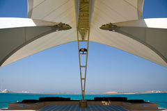 Modern Abu Dhabi structure framing sea and island. Modern sail like construction providing shade and framing a view of gulf and distant sand dunes stock photos