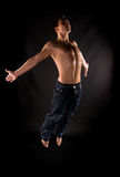 Modern acrobat jumping. In front of black background royalty free stock photography