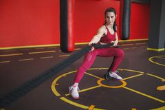 Confident adult woman training with battle ropes stock images