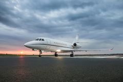 Modern advanced private business jet ready to take off. With sunrise in the background and clouds above airplane royalty free stock image