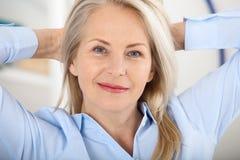Modern affärskvinna Den härliga mitt åldrades kvinnan som ser kameran med leende, medan placera i kontoret arkivfoto