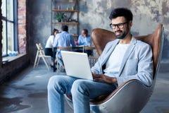 Modern affärsman med ett bärbar datorsammanträde i en stilfull bekväm stol arkivbilder