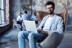 Modern affärsman med ett bärbar datorsammanträde i en stilfull bekväm stol arkivfoton