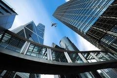 Modern aff?rsmitt i Hong Kong Skyskrapor i kommersiellt område med flygplanet som över flyger på Hong Kong askfat arkivbilder