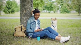 Modern African American girl is listening to music with headphones and using smartphone relaxing in city park with pet. Modern African American girl is listening stock video footage