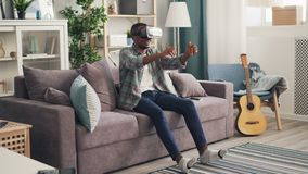 Modern African American guy is playing game in virtual reality glasses driving car racing sitting on sofa alone and. Modern African American guy is playing cool stock video footage