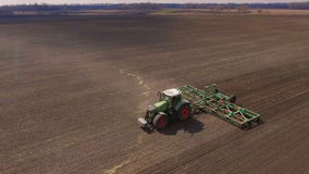 Modern agribusiness. Tractor cultivates the land in the field in early spring stock video footage