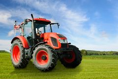 Modern agricultural tractor in the field. Composite image of a modern red agricultural generic tractor on a green field on a sunny day stock image