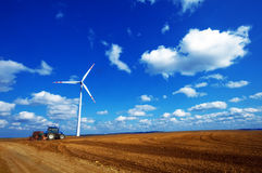 Modern agriculture, wind turbine and tractor Stock Photography