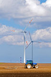 Modern agriculture, wind turbine and tractor Royalty Free Stock Photo