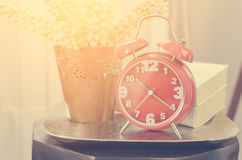 Modern alarm clock on tray with book and plant Royalty Free Stock Photography
