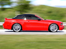 Modern American Red Convertible. A modern red american convertible speeding by on the road Stock Images