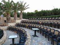 Modern amphitheater plastic chairs and palm trees in Greece Royalty Free Stock Photos