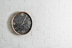 Modern analog clock hanging on white wall, space for text. Time of day stock images