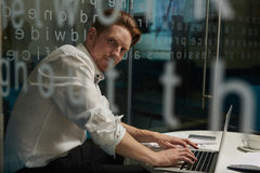 Modern analyst. Busy director sitting in office at night and analyzing online data royalty free stock photography