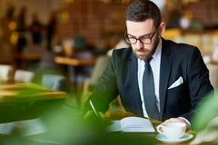 Modern analyst. Elegant trader sitting in cafe and making notes in notebook royalty free stock images