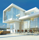 Modern angular luxury tropical villa. Modern angular whitewashed luxury tropical villa with huge glass windows overlooking a paved patio with an outdoor living Royalty Free Stock Photo