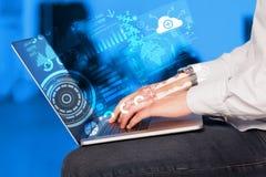 Modern anteckningsbokdator med framtida teknologisymboler Arkivfoto