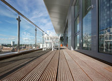 Modern Apartment Balcony with Wooden Decking. Penthouse apartment balcony with chrome and glass railings and views over city Royalty Free Stock Image