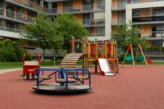Modern apartment building with children`s outdoor playground. In a natural light stock photo